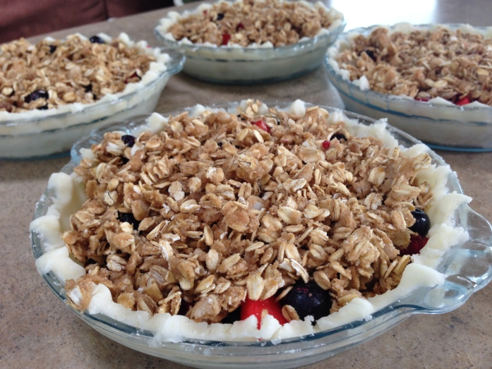Father's Day desserts ready to go in the oven. Mixed fruit pies with streusel topping.