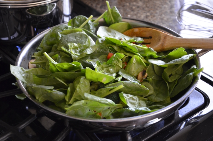 When the veggies are aldente, add a heaping couple of handfuls of fresh spinach and grate a clove of garlic over it.